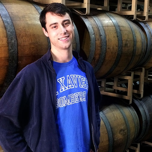 Cole Dennis standing in front of wine barrels