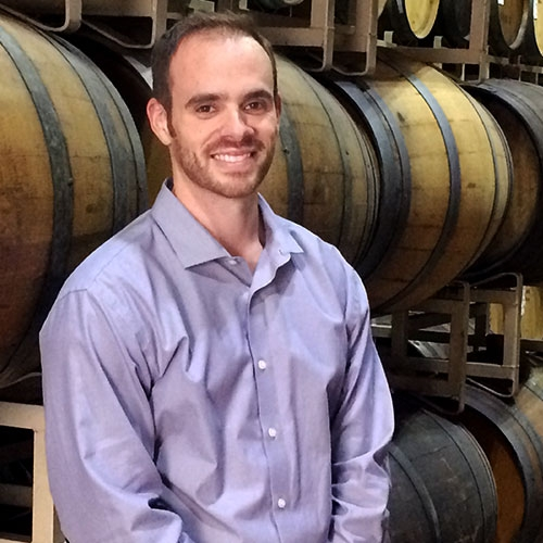 Colin Hough with a big smile standing in front of wine barrels
