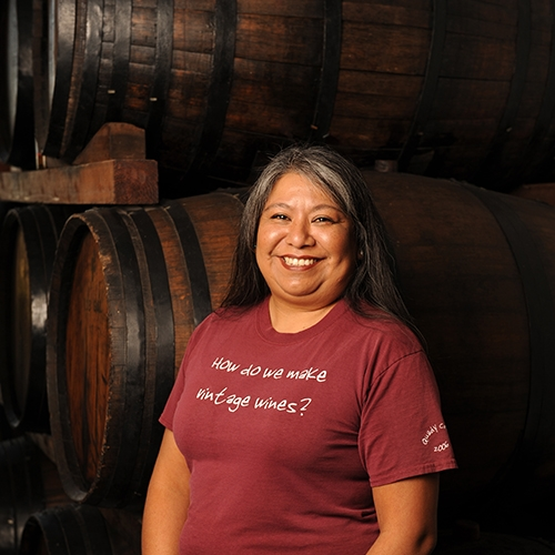 Cynthia Leon in front of wine barrels at Quady Winery in Madera, California.