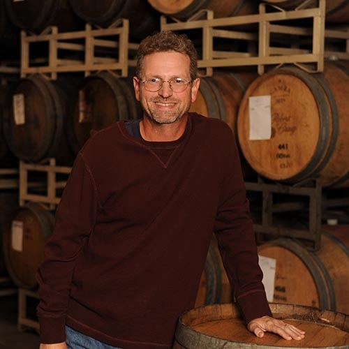 Darin Peterson in front of wine barrels at Quady Winery in Madera, California.
