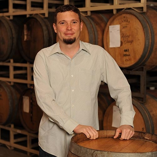 Dave Glover in front of wine barrels at Quady Winery in Madera, California.