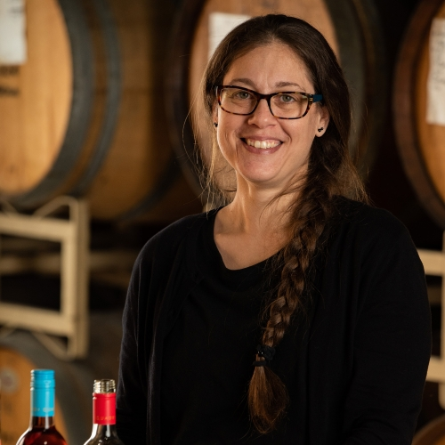 Andrea Milliorn, Senior Accountant at Quady Winery, holding a glass of Electra Moscato in front of a wall of wine barrels.