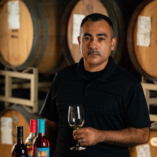 Juan Cuevas, Cellar Master, holding a glass of wine and standing next to bottles of Electra Moscato wine.