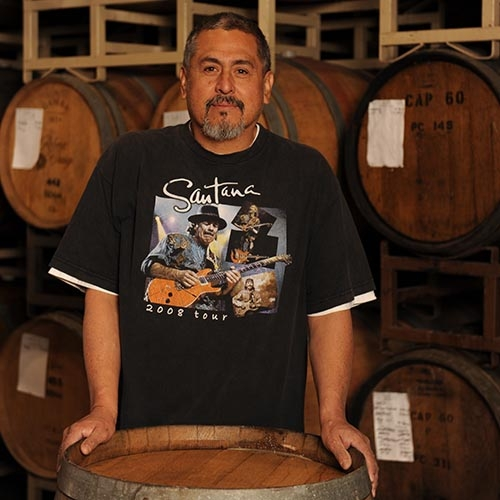 Mauro Molina in front of wine barrels at Quady Winery in Madera, California.